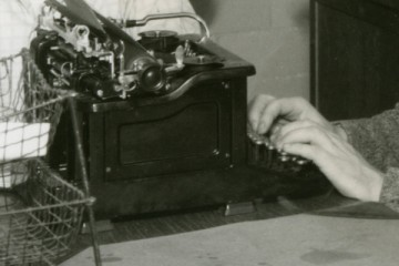 several Aquin student staff at typewriters and on the telephone
