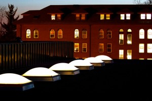 Grace Residence Hall is seen at sunset with the skylights of McCarthy gym in the foreground.  Taken April 11, 2011 from the top of the Anderson Parking Facility.