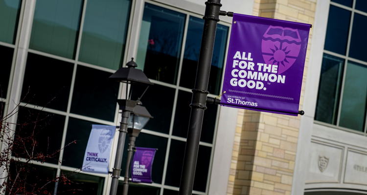 "A sign reading ""All for the Common Good"" hangs from a lamp post on the John P. Monahan Plaza January 29, 2016. The Anderson Athletic and Recreation Complex is in the background."