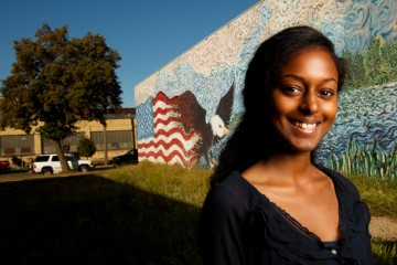Undergraduate Justice and Peace Studies major Heaven Fekadu stands in front of a mural she helped paint in south Minneapolis. Photo by Mike Ekern '02.