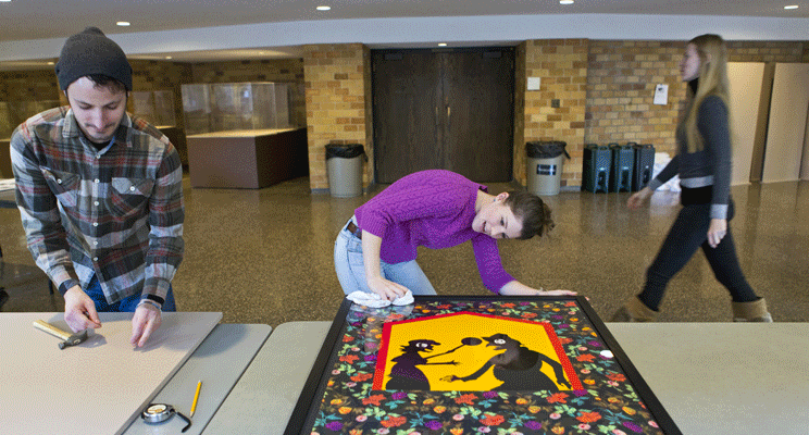 """Graduate art history students prepare works from the Dolly Fiterman collection for the """"Insights Into Modern Art"""" exhibtion that can be seen in the O'Shaughnessy Educational Center through May 26. From the left are Brady King, Lauren Greer and Olga Ivanova."""