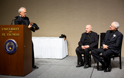 Father John Malone, left, cracks a joke as Archbishop Emeritus Harry Flynn and Father Dease look on.