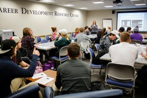 Career Specialist Amber Bieneck Thom (middle back) talks to students during a job and internship fair orientation event at the Career Development Center's Career Development Resource Center in the Murray-Herrick Campus Center on December 15, 2014. Students attended the event to learn about and register for the spring Job and Internship Fair.