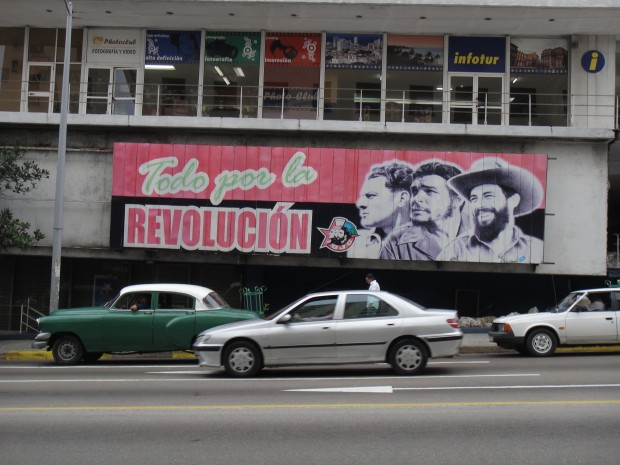 A typical picture of a propaganda billboard in Havana with the leaders of the Cuban revolution. A green maquina, a 1950s-era American car used for public transportation is stationed beneath it. Photo courtesy of Peter Scheerer.