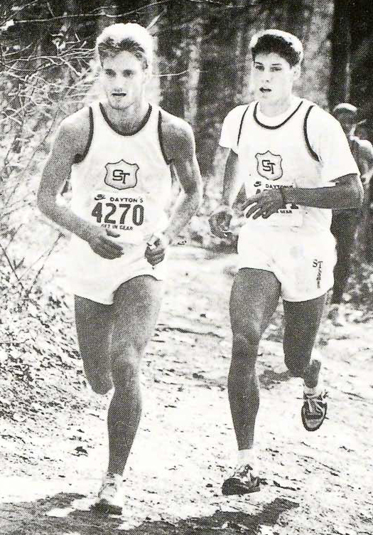 Mike Johnson '90, right, running with teammate Mike Brown in a November 1987 cross country meet, earned All-American honors in cross country and track at St. Thomas. (Aquin photo by Patty Varley)