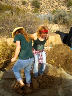 Meredith Heneghan '16, left, and Alyssa Adkins '15 mix cob, the material used to construct buildings and other structures at Quail Springs. Cob is a mixture of sand, clay, hay and water.