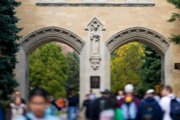 A statue of Saint Thomas Aquinas on Aquinas Hall (AQU) is shown as students walk through the arches. Taken September 26, 2007.