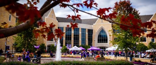 Fans fill the John P. Monahan Plaza for Purple on the Plaza before the Tommie Johnnie football game September 21, 2013. The Anderson Student Center is in the background and fall leaves on a tree are in the foreground.St. Thomas would lose to Saint John's 18-20.