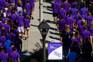 "Incoming freshmen walk across the lower quad past clapping faculty and staff during the freshman March Through the Arches September 2, 2014. A ""Think Critically"" mission sign is prominently featured."