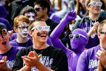 St. John Vianney seminarians (including one covered entirely in purple) cheer during a football game against the University of Wisconsin-La Crosse September 13, 2014 in O'Shaughnessy Stadium. The Tommies won 46-0.