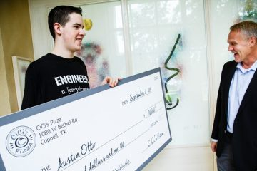 Austin Otto (Mechanical Engineering) holds a $10,000 check with CiCi's Pizza CEO Darin Harris, right, on September 2, 2015 in the Owens Science Hall in St. Paul. Austin Otto won $10,000.00 through the CiCi's Pizza Photo Scholarship Contest. Otto wrote an essay and snapped a picture of himself in a CiCi's Pizza restaurant. He initially thought he was being interviewed about his 3D Printing engineering research and was surprised by his parents with the check after CiCi's CEO Darin Harris announced that he had won the scholarship.