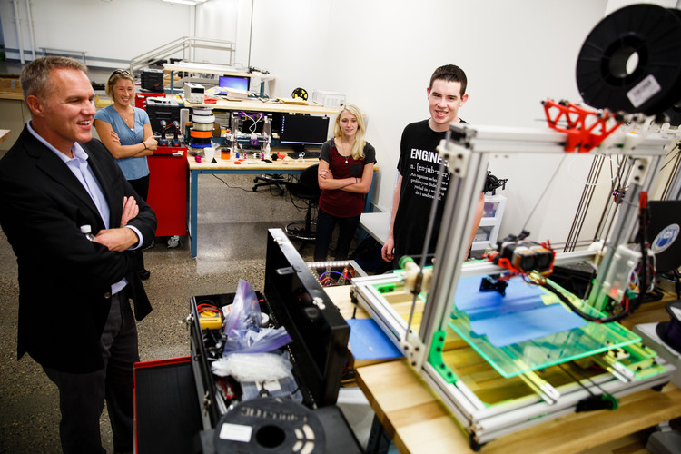 Austin Otto (Mechanical Engineering) far right, talks with CiCi's Pizza CEO Darin Harris, far left, as Engineering Professor Brittany Nelson-Cheeseman, back left, and Lindsey Bollig (Mechanical Engineering), back right, look on on September 2, 2015 in the Facilities and Engineering Building on south campus in St. Paul. Austin Otto won $10,000.00 through the CiCi's Pizza Photo Scholarship Contest. Otto wrote an essay and snapped a picture of himself in a CiCi's Pizza restaurant. He initially thought he was being interviewed about his 3D Printing engineering research and was surprised by his parents with the check after CiCi's CEO Darin Harris announced that he had won the scholarship.