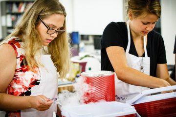Students Lauren Van Beek (mechanical engineering), left, and Rachel Gehlhar (mechanical engineering) right, scoop dipping dots out of liquid nitrogen at the Playful Learning Lab Expo in the Facilities and Design Center on south campus in St. Paul on September 8, 2015. The event, organized by the School of Engineering and Professor AnnMarie Thomas included several stations with on-demand engineering demonstrations.