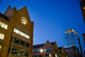 The glowing clock tower of Terrence Murphy Hall is seen against the Minneapolis skyline the night of October 5, 2015.