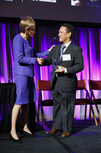 """Pedro """"Sonny"""" Ada, president of Ada's Trust and Investment, located in Guam, receives the Family Business award from UST President Dr. Julie Sullivan during the 2015 Entrepreneurship Awards gala in the Schulze Grand Atrium in the School of Law building in downtown Minneapolis on November 19, 2015."""