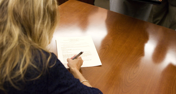 Assistant Dean for External Relations Lisa Brabbit signs diplomas after The Swearing in Ceremony of School of Law Clinical Law Students in The Frey Moot Courtroom. Taken August 24, 2007.