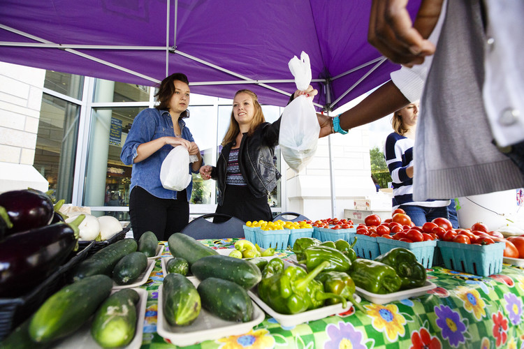 Student volunteers Marnie Sciamanda (Biology) and Ashley Brundrett (Biology) sell produce at the St. Thomas Farmers Market.