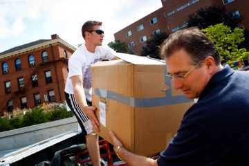 "A member of ""Father Dease's Moving Crew"" (left) helps a parent pull a box out of a truck during move-in day September 3, 2011."
