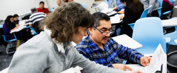 Theology professor Anne Attea helps a student during a Hispanic Lay Ministry class. Photo by Mike Ekern '02.