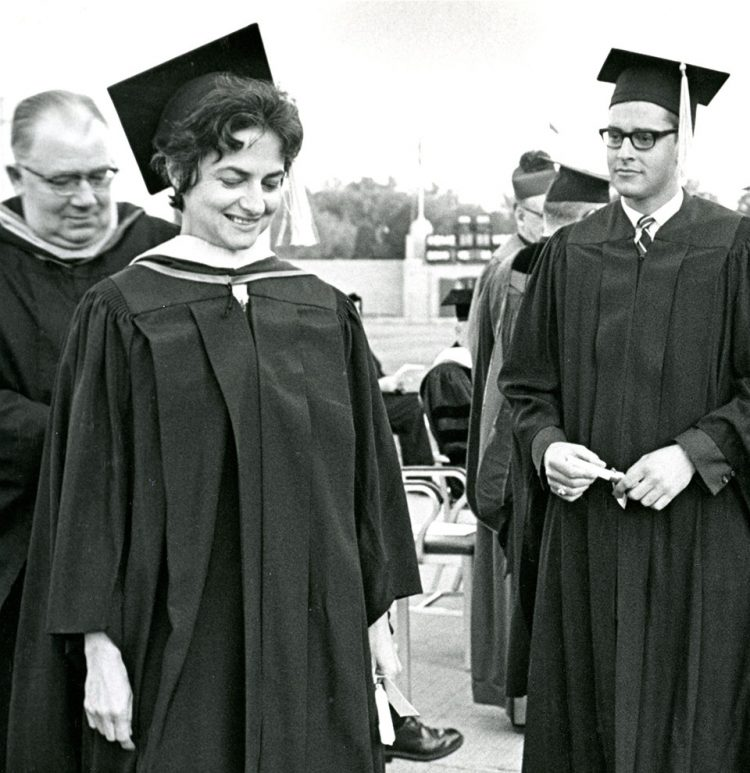 Master of Education student Penninah Silverberg receives her academic hood from Leonard Hauser at the College of St. Thomas commencement ceremony, June 1966. Lee Simmons looks on.