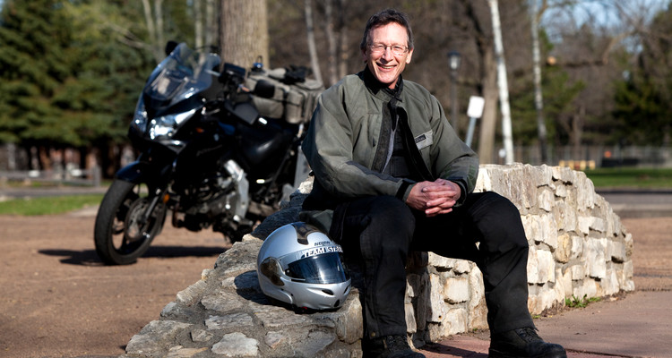 """University Relations Director of News Services Jim Winterer and avid motorcyclist poses for a photograph near South Mississippi River Boulevard in Saint, Paul, Minn., on Friday, April 9, 2010. Winterer is photographed for the """"How We Work, How We Play"""" section of the Spring 2010 edition of St. Thomas Magazine."""