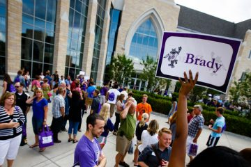"""A student orientation leader holds up a """"Brady"""" sign, indicating where a tour group should assemble July 28, 2014 on the John P. Monahan plaza during orientation and registration."""