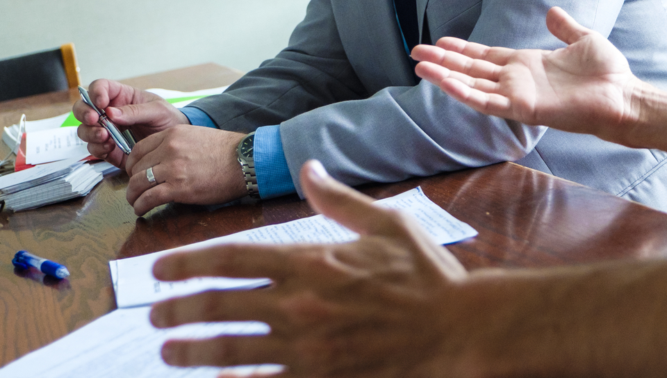 Hands on a table during a meeting