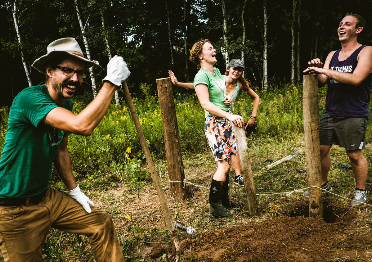 Jake Kulju '04, Meredith Heneghan '16, Natalie Thoresen and Aaron Pietrowski laugh as they build a fence on Kulju's farm.