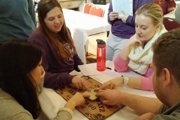"Classmates in the 2015 J-Term course ""Spooks, Psychics and Skeptics in the UK"" experiment with a Ouija board. (Photo courtesy of Greg Robinson-Riegler)"