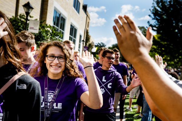 St. Thomas students high-five during March Through the Arches, an example of what makes Minnesota the happiest state.