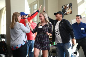 Sophomore Megan Sharkus (center) celebrates with her teammates after they're announced the winner of the US Bank Make-a-Thon.