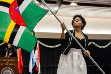 Chelsea Balthazar waves the flag of Dominica at the 28th Annual International Dinner in Woulfe Hall on April 1, 2017.