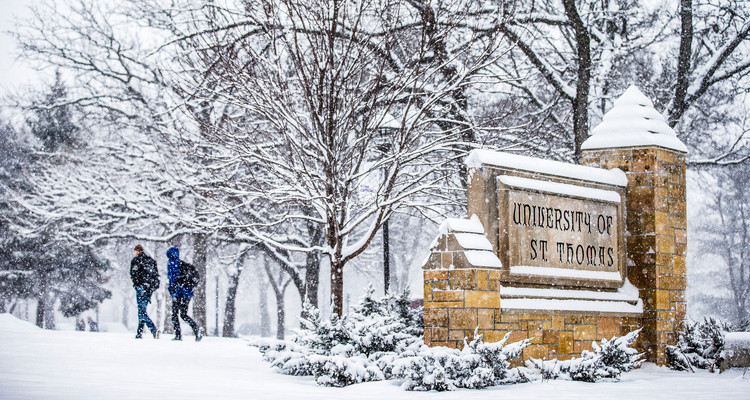 "Students walk amid falling snow past the ""University of St. Thomas"" monumental sign at the corner of Summit and Cretin Avenues February 2, 2016."