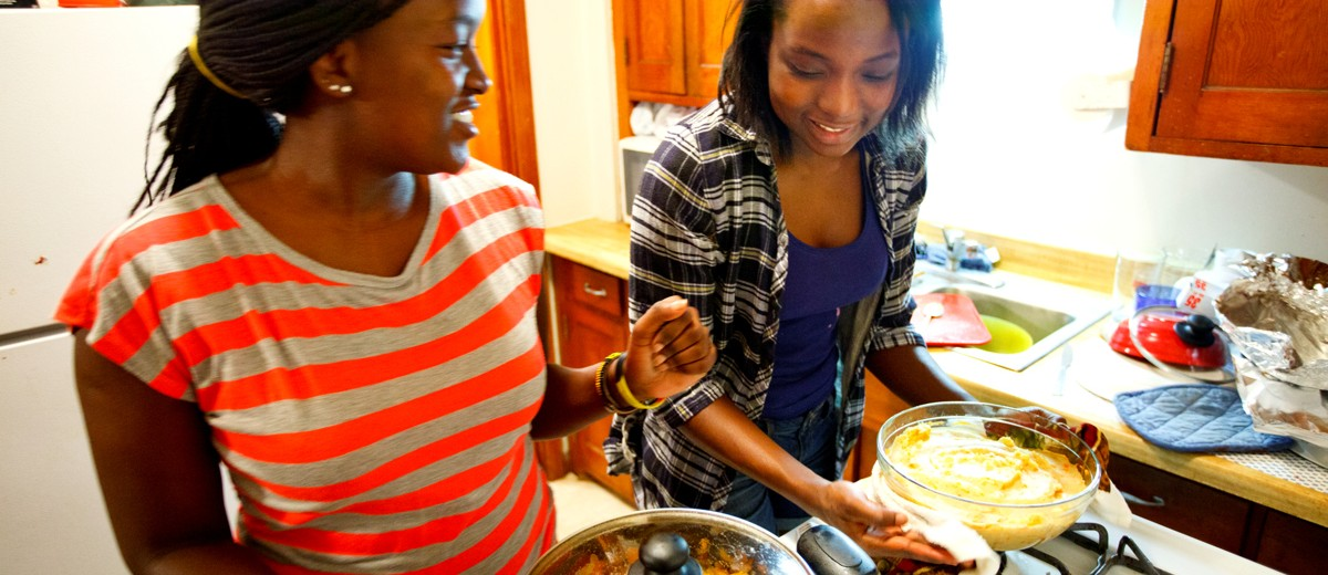 """Olivia, right, is the acknowledged cook of the two sisters. That means unannounced visits by Felista, who lives one floor up from Olivia in the same apartment building, are always a possibility. """"When you turn 12, you're taught how to cook,"""" Olivia said. """"Whoever finishes [grade seven] at my house has to cook food for the family for a week. If you burn it, you cook again until you become perfect. In Uganda it's not a common thing for boys to cook."""