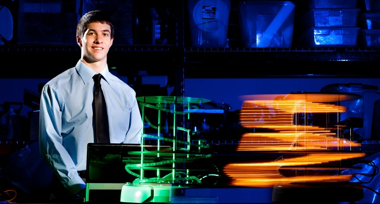 """Electrical engineering student Ryan Delaney shows off his project team's """"Turtlebot,"""" July 19, in the basement of O'Shaughnessy Science Hall. (Photo by Mike Ekern '02)"""