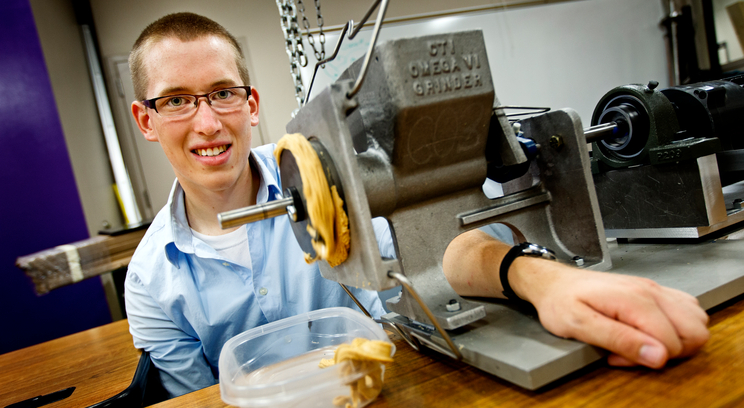 Mechanical engineering student Noel Naughton with the Omega VI peanut grinder used to make peanut butter for his and Dr. Jim Ellingson's summer research project. Photo by Mike Ekern '05.