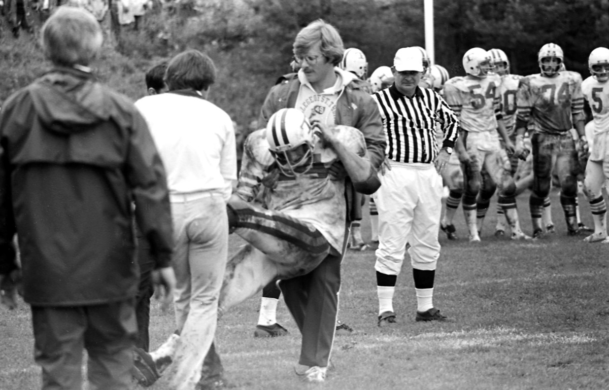 Offensive line coach Mark Dienhart assists a player off the field at St. John's in 1977.