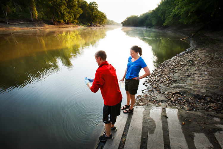 University of St. Thomas chemistry professor Dr. Kristine Wammer, right, and chemistry major Dan Kellen, left, collect a water sample from the Minnesota River on August 27, 2012, at Land of Memories Park in Mankato. Wammer and her students test collected samples to research the role of low-level antibiotic concentrations on development of antibacterial resistance in environmental microorganisms. (Photo by Mark Brown)