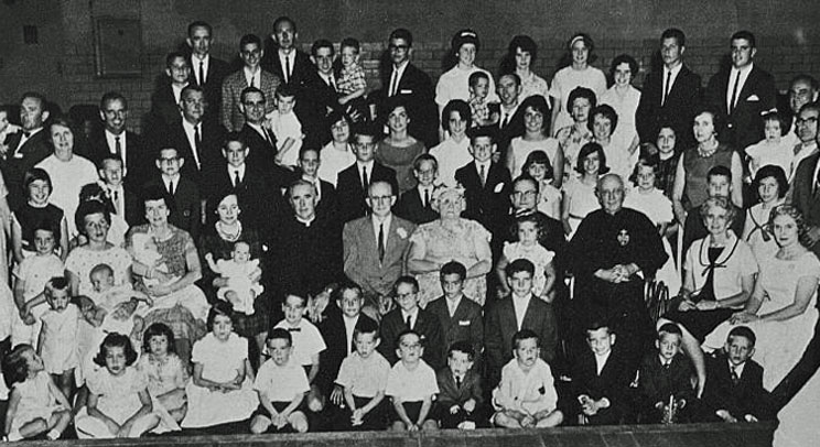 Never mind about Waldo … where's Bernard Vincent Brady? This 1963 photo of a large Irish family has three of them. The youngest Bernard Vincent Brady in the photo is familiar to the University of St. Thomas community; now chair of the university's Theology Department, he is the boy wearing a bowtie in the second row and fifth from the left.  The woman who is holding a baby behind him is his mother, Nora (Leneghan) Brady from County Mayo, Ireland.  The priest directly behind him is his uncle, the second Bernard Vincent Brady. To the right of the priest are the bowtie boy's grandparents, Emmet and Ethel (Kalaher) Brady, who were celebrating their golden wedding anniversary. The priest seated to the right of Emmet and Ethel is Leo Patrick Brady, C.P., and the priest to the right of Leo is the third Bernard Vincent Brady, C.P.  This clan of Bradys originally came from County Clare in Ireland. The family photo was taken at a parish hall in Akron, Ohio.