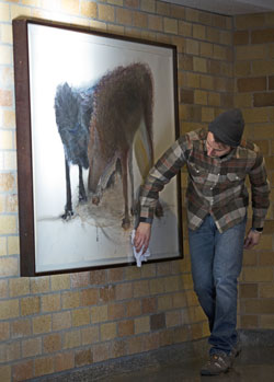 Art history graduate student Brady King prepares artwork from the Dolly Fiterman collection for display in the O'Shaughnessy Educational Center lobby gallery.