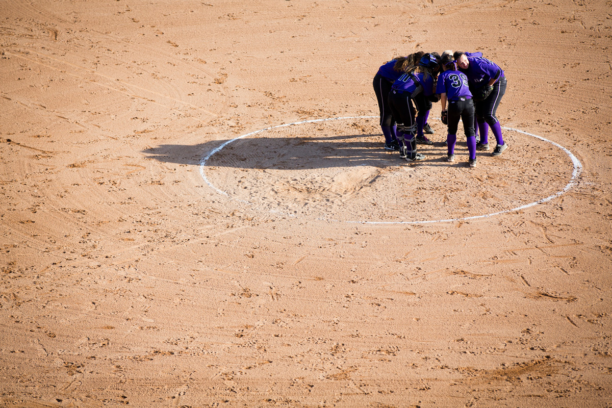 The Tommies huddle during a softball game against Macalester College on April 25, 2013. (Photo by Mark Brown)