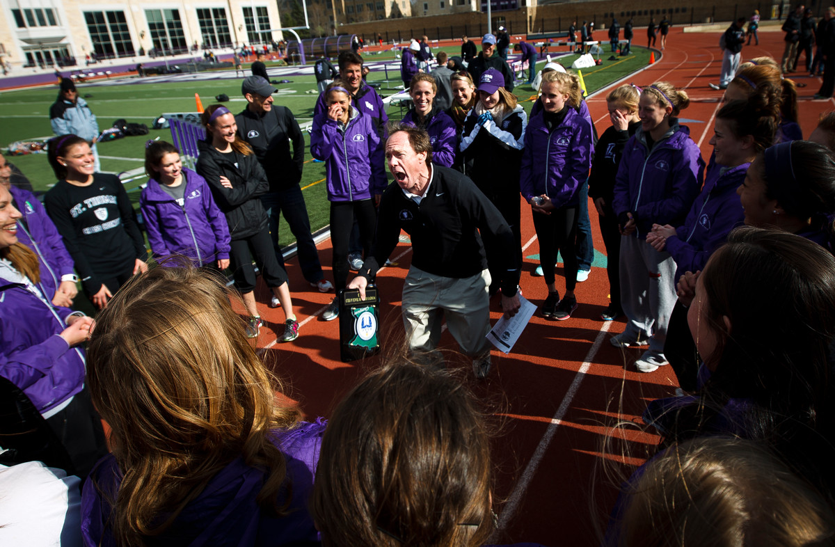 Women's track and field head coach Joe Sweeney exults in victory while holding his team's first place plaque following the women's MIAC outdoor track and field championship finals May 11, 2013. (Photo by Mike Ekern '02)