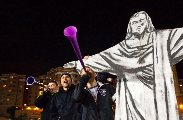 SJV seminarians Andrew Riedl, Nelson Quintanilla and Eric Brandt cheer on the JAXX from beneath the arm of a cardboard cutout of Jesus during the 2009 Rector's Bowl.