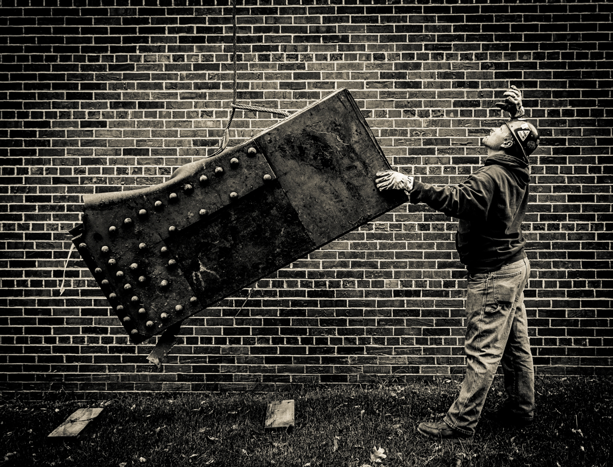 A worker guides a piece of debris to the ground behind Brady Education Center where it will rest until it finds a final home near the Frey Science and Engineering Center. (Photo by Mike Ekern '02)