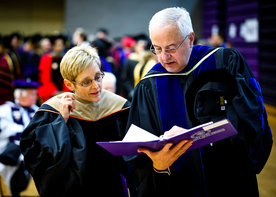 President Julie Sullivan, and president emeritus Fr. Dennis Dease look over their script in Schoenecker Arena prior to the ceremony. (Photo by Mike Ekern '02)