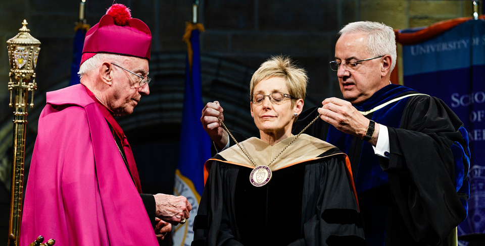 President emeritus Fr. Dennis Dease (right) puts the chain of office around President Julie Sullivan's neck as Archbishop emeritus Harry Flynn looks on during the inauguration of Sullivan as the 15th president of St. Thomas on Oct. 17 in the Anderson Athletic and Recreation field house. (Photo by Mike Ekern '02)