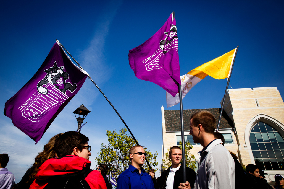Students holding St. Thomas flags hang out on the John P. Monahan Plaza during the community lunch prior to the inauguration (Photo by Mark Brown)