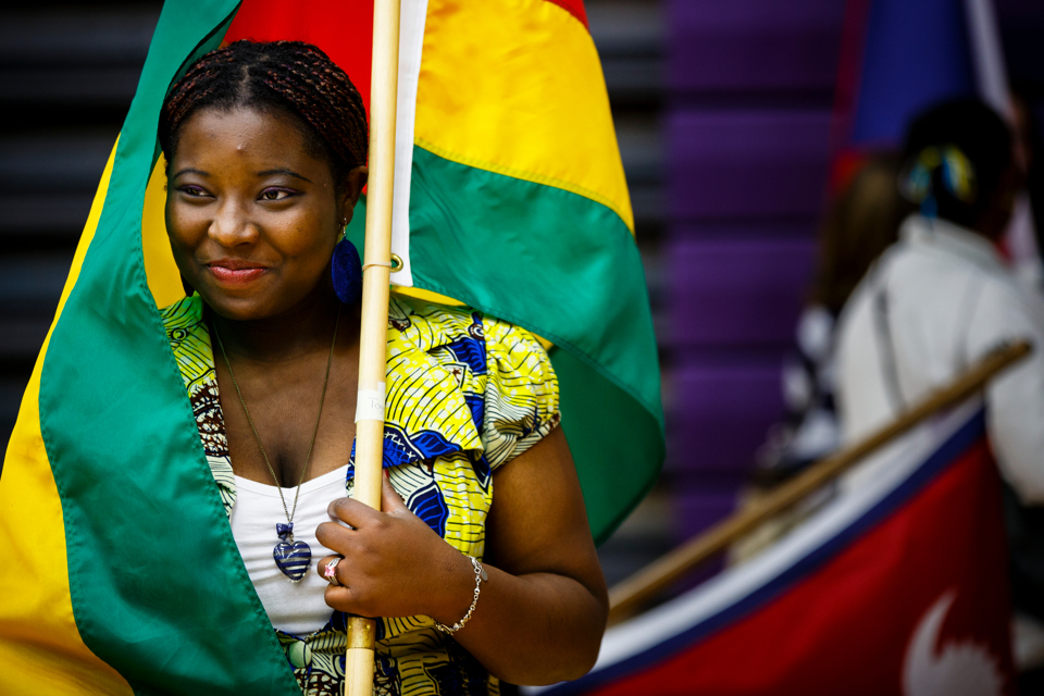 Flag bearer and student Natacha Eguida smiles while wrapped in the flag of her native Togo in Schoenecker Arena prior to the inauguration. (Photo by Mark Brown)