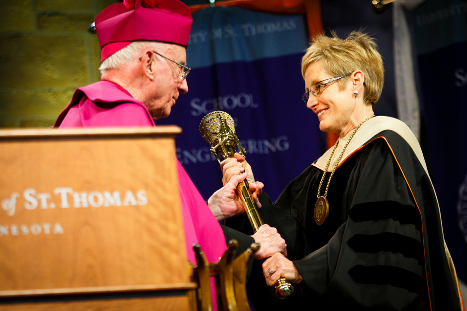 Archbishop Emeritus and trustee Harry Flynn hands the presidential mace to President Julie Sullivan. (Photo by Mark Brown)