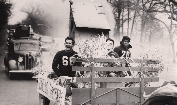"Homecoming float featuring a smokehouse and a banner which says ""Smoke out the Pipers."" Football players Tom Preston (left) and Nick Combs (right) are seated on float. From the University Archives photo collection."